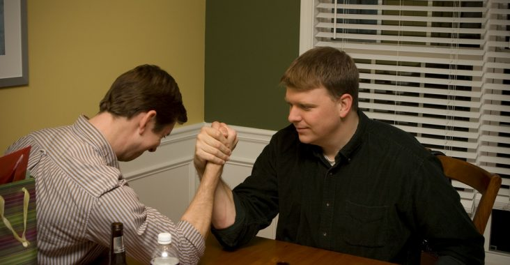 """An image of two guys arm wrestling. This is infighting I push back against in my talk """"Out of the Silos and Into the Farm"""""""