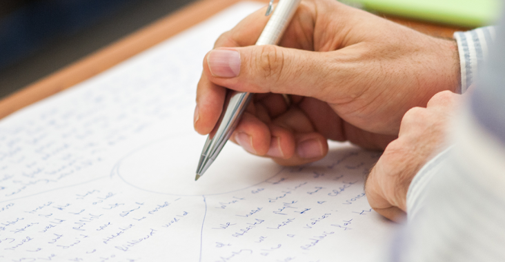 An image of someone writing with pen on paper