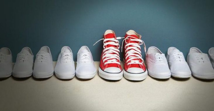 Red sneakers in a line of white sneakers