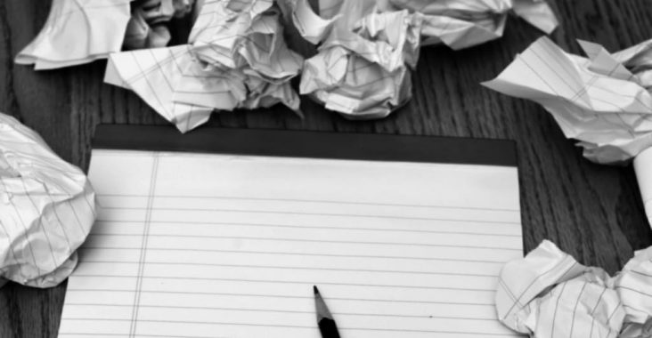 A photo of crumpled pages around a pad of paper